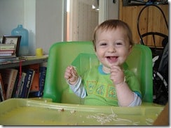 baby in a green highchair eating spaghetti