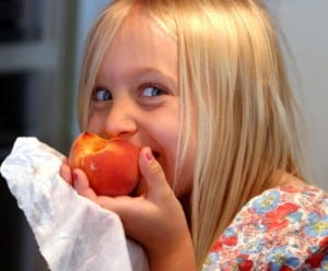 Blonde girl eating peach