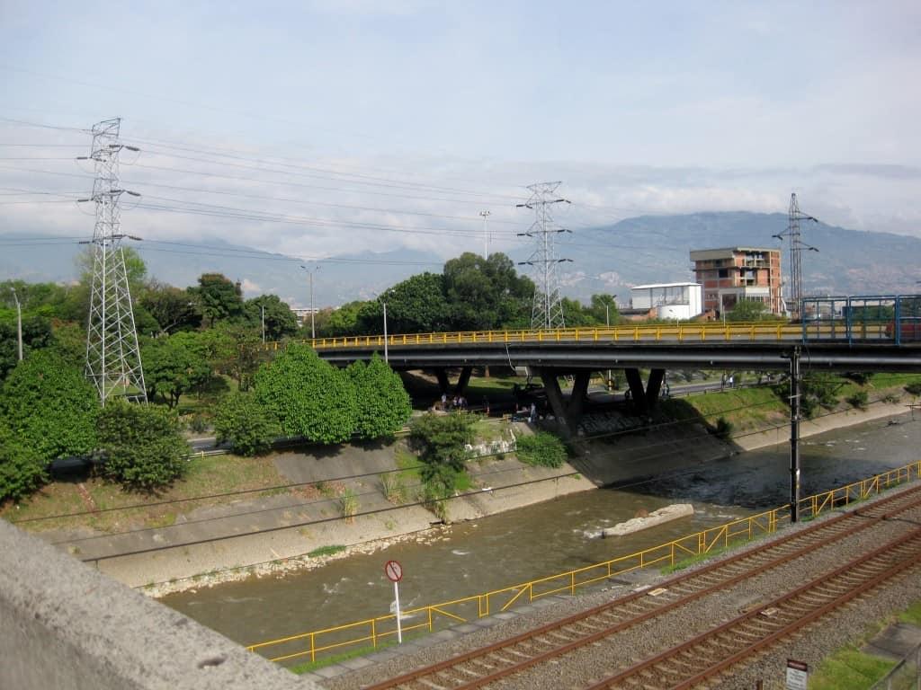 river, train tracks, bridge with Medellin hills in background